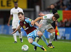 Burnley's Ashley Barnes (left) and Leeds United's Gaetano Berardi battle for the ball during the Carabao Cup, third round match at Turf Moor, Burnley.
