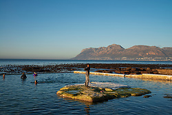 People swim as a worker removes slippery algae by painting lime wash on a rock in the Dalebrook tidal pool in Kalk Bay. While public spaces, in theory, are closed under Level 3 lockdown regulations, much of the public seemed to have decided that these spaces are now open. Workers could also be seen tidying up some of these spaces today, Wednesday June 24, 2020. The city of Cape Town has appealed to the national government to ease the lockdown on public spaces, and it appears they may be preparing for re-opening. PHOTO: EVA-LOTTA JANSSON