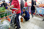 Shoppers crowd into New Mart, a local competitor of Tesco, in Fushun, Liaoning Province, China on 07 October  2012.  An elderly farmer squats on the check out line waiting to pay for a jog of cooking oil at a Tesco in Fushun, Liaonin Province, China on 08 October 2012. After a period of rapid early success, many western retailers are finding it increasingly difficult to make inroads to the Chinese market,