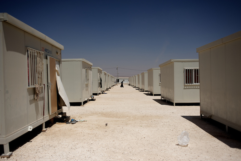 August 09, 2013 - Zarqa, Jordan: A syrian refugee passes by a row of portacabins at the Mrigb Al-Fuhud refugee camp, also known as Emirates-Jordanian camp, 20 kilometres east of the Jordanian city of Zarqa.<br /> The 10 million USD camp, which has 750 caravans, a hospital, and a school and can take up to four thousand people, first opened in April 2013 and was paid for by the United Arab Emirates. Work is underway to house a total of 20 thousand by the end of the year.<br /> In contrast with the two other camps in the area, Mrigb Al-Fuhud as been classified by many as a 'five star' camp due to impressive housing facilities provided to the refugees. (Paulo Nunes dos Santos/Al Jazeera)