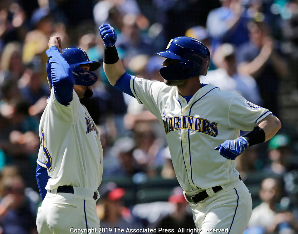 Seattle Mariners' J.P. Crawford, left greets Mitch Haniger after scoring on Haniger's two-run hime run on a pitch from Minnesota Twins' Kyle Gibson during the fifth inning of a baseball game, Sunday, May 19, 2019, in Seattle. (AP Photo/John Froschauer)