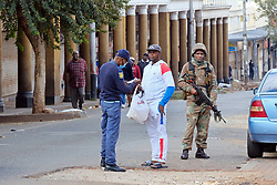JOHANNESBURG, SOUTH AFRICA - APRIL 18: A man os searched by a SAPS officer during a South African Police Service (SAPS) Metro Police and Army supported patrol in Rockey Street, Yeoville. Random searchs and social distancing measures on April 18, 2020 in Johannesburg South Africa. Under pressure from a global pandemic. President Ramaphosa declared a 21 day national lockdown extended by another two weeks, mobilising goverment structures accross the nation to combat the rapidly spreading COVID-19 virus - the lockdown requires businesses to close and the public to stay at home during this period, unless part of approved essential services. (Photo by Dino Lloyd)