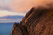 Granite cliffs rise above the coast near Bunes Beach, Moskenesoya, Lofoten Islands, Norway.