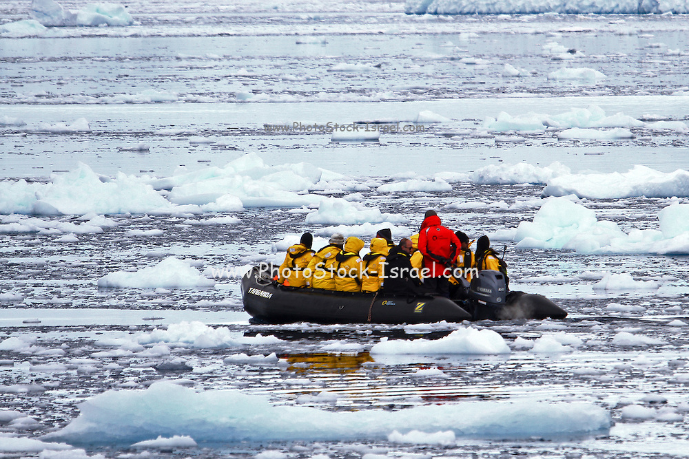 tourists on a rubber Zodiac dinghy sailing through ice in the water