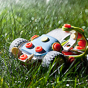 A colourful children's toy car sitting in long grass in the garden in a rain storm