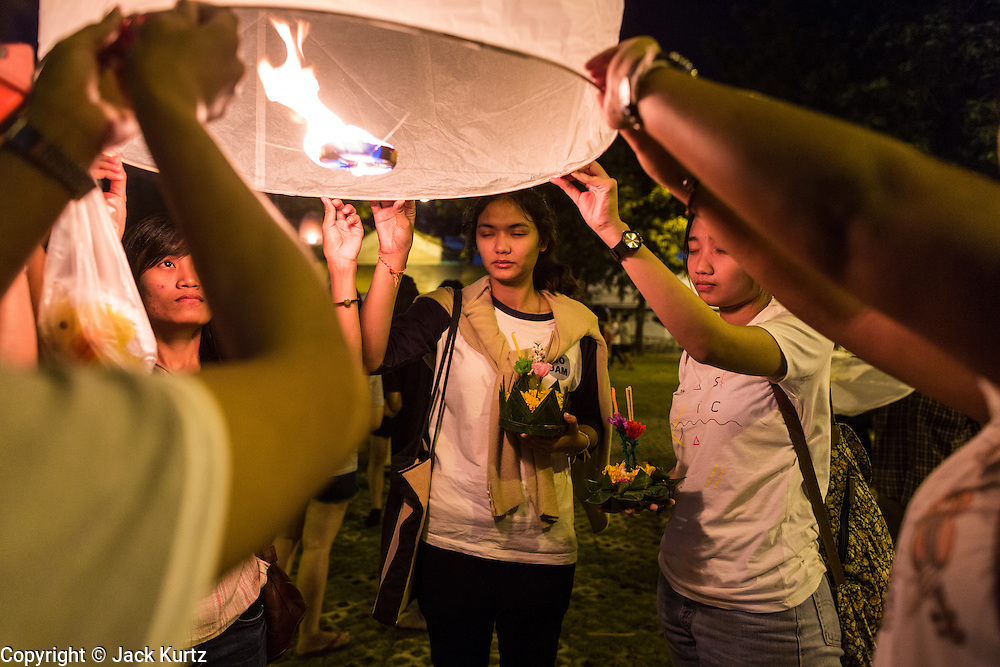 """17 NOVEMBER 2013 - BANGKOK, THAILAND: Students pray before launching  a Yi Peng lantern on Loy Krathong near Wat Yannawa in Bangkok. The Yi Peng lanterns are Loy Krathong tradition in Chiang Mai but they are becoming more popular  in Bangkok and central Thailand. Loy Krathong (also written as Loi Krathong) is celebrated annually throughout Thailand and certain parts of Laos and Burma (in Shan State). The name could be translated """"Floating Crown"""" or """"Floating Decoration"""" and comes from the tradition of making buoyant decorations which are then floated on a river. Loi Krathong takes place on the evening of the full moon of the 12th month in the traditional and they do this all evening on the 12th month Thai lunar calendar. In the western calendar this usually falls in November. The candle venerates the Buddha with light, while the krathong's floating symbolizes letting go of all one's hatred, anger, and defilements       PHOTO BY JACK KURTZ"""