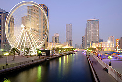 Evening view of Eye of the Emirates ferris wheel and Al Qasba entertainment district in Sharjah United Arab Emirates