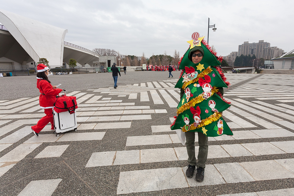 A participant, dressed as a Christmas tree takes part in the Tokyo Great Santa Run in Komazawa-daigaku Olympic Park, Tokyo, Japan. Sunday December 22nd 2019, The great Santa Run was first run in Tokyo in 2018. This years run saw over 3,000 people in Santa costumes run and walk a 4.3 kilometre course to raise money for medical charities in japan and water projects for the Maasai in Kenya.