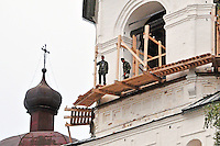 With no safety equipment in place, restorers build scaffolding six stories up near a bell tower of the Kirillo-Belozersky Monastery near Kirillov, once one of the largest in Russia. Founded in 1397 by St. Kyrill (St. Cyril) and strategically located on the banks of Lake Siverskoye, the complex has two priories and eleven churches, protected by walls twenty feet thick. During its turbulent history, the remote, well-fortified monastery became a place of exile for many dissenters. Now a museum protecting invaluable religious icons, it is undergoing slow but steady restoration.