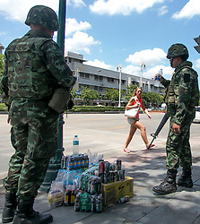 © Licensed to London News Pictures. 23/05/2014. A foreign tourist walks past two Thai Army soldiers in Bangkok. Thailand's army said on May 23 that 155 prominent figures, including Yingluck and ousted government leaders, were banned from leaving the country without permission following a military coup.  Photo credit : Asanka Brendon Ratnayake/LNP
