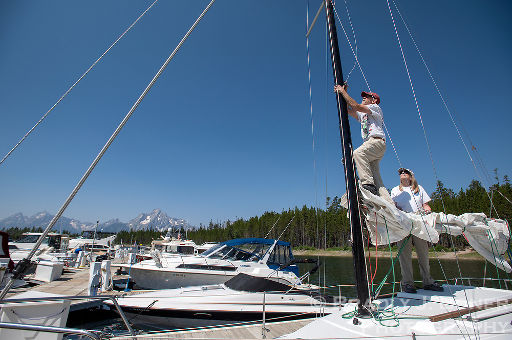 Joe and Betsy Bernfeld of Wilson set up the rigging on their sailboat Friday at the Colter Bay Marina in Grand Teton National Park. The Bernfelds, who weren't able to dock their boat at their Colter Bay slip until Tuesday, found out Wednesday they would have to take it out again by the end of the month. Rapid drawdown of Jackson Lake due to due to demand for water from farms in Idaho will likely force most operations at the marina to cease by July 31.