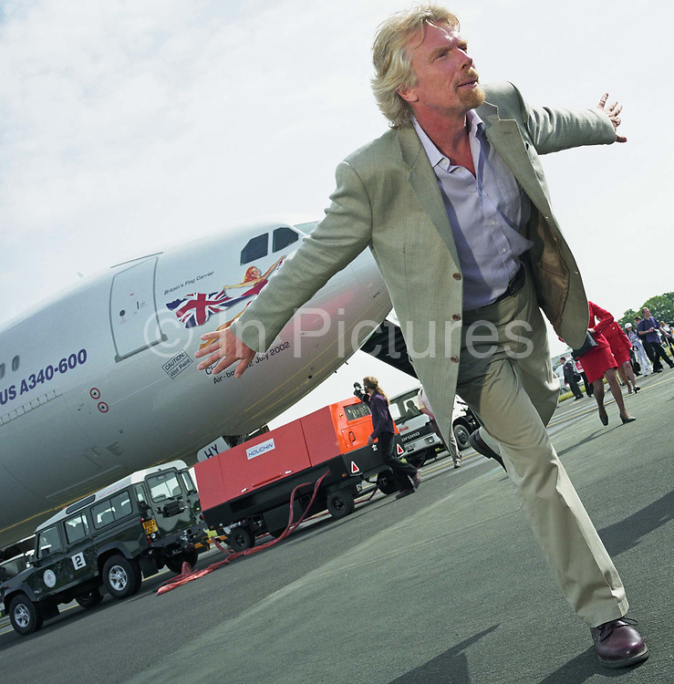 Virgin Chairman Sir Richard Branson performs in front of the media during a publicity launch of Virgin Atlantic's new Airbus A340-600 which is parked behind the business tycoon during the Farnborough Air Show in Hampshire, England. He stands on one leg in a typically eccentric aviation-owner balancing trick. Behind him near the aircraft's nose a Virgin 'babe' echoes his outstretched arms while flying the British Union Jack flag. Farnborough centres its presence on big aerospace business to the tune of $40bn in orders and industry leaders like Branson, Boeing and Airbus parade their brands and announce new orders throughout the week-long display. Picture from the 'Plane Pictures' project, a celebration of aviation aesthetics and flying culture, 100 years after the Wright brothers first 12 seconds/120 feet powered flight at Kitty Hawk,1903.