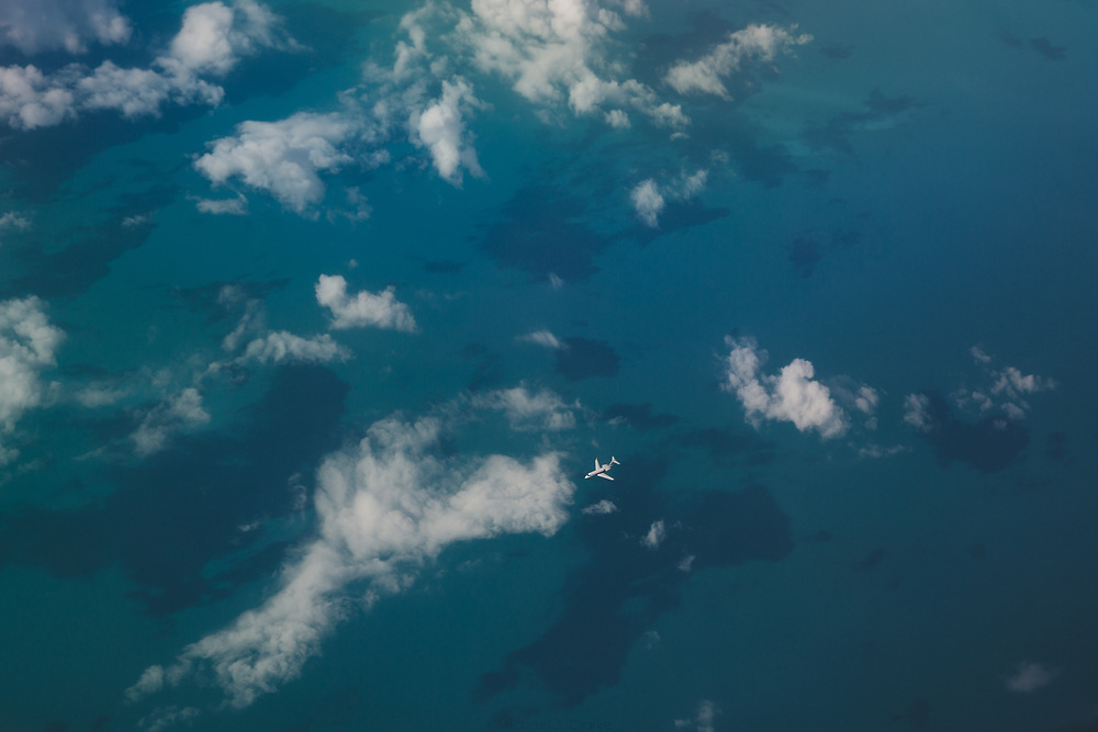 A business jet cruising over the waters of The Bahamas on a warm spring afternoon.