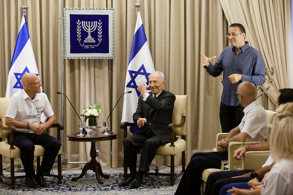 Israel's President Shimon Peres (C) uses sign language to greet members of Israel's National Deaflympic Team who will represent Israel at the upcoming Deaflympic Games which will be held in Sofia, Bulgaria in July 2013, during their meeting at the President's Residence in Jerusalem, Israel, on May 27, 2013.