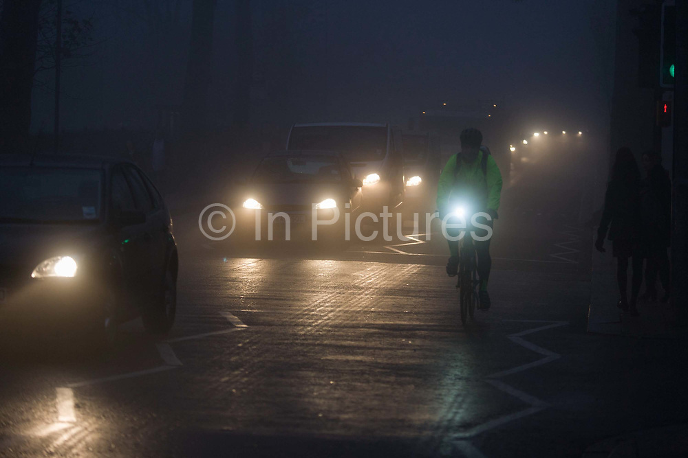 A well-lit cyclist and commuter traffic at dawn on a foggy morning in south London. Wearing a high-visibility jacket and a flashing strobe light on his handlebars, as recommended by safety campaigners and the police, he can be seen by motorists during rush-hour. It is dawn at around 8.45 on this winter morning, a dark and miserable time of day in this south London suburb from where Londoners start their journeys north into the City. Cars and trucks wait for the lights to change, their headlights shining in the dispersing fog on Denmark Hill.