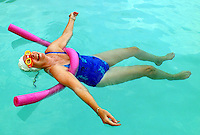 Laughing woman floating in pool with bright pink noodle and swim cap and goggles