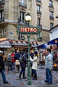 Tourists walk past Metro sign in Boulevard Saint Germain, central Paris, France