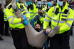© Licensed to London News Pictures. 01/09/2020. London, UK. Police remove a handcuffed Extinction Rebellion protester from a demonstration in Parliament Square. The environmental activist group intend to peacefully blockade the Houses of Parliament until Parliament agrees to debate their three demands.  Photo credit: George Cracknell Wright/LNP