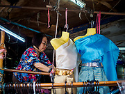 28 MAY 2018 - BANGKOK, THAILAND: A woman who sells traditional Thai clothing sets up her shop in Phra Khanong Market in Bangkok. The market serves a mix of Thai working class people and immigrants from Myanmar (Burma).      PHOTO BY JACK KURTZ
