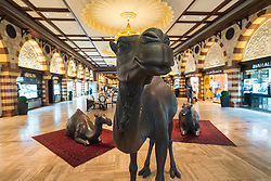 Life-size camel sculptures inside Middle Eastern styled The Souk shopping district inside the Dubai mall in Dubai United Arab Emirates