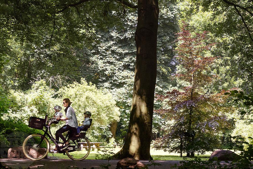 Bij Rhijnauwen fietst een jonge moeder met twee kinderen met fietshelmen op de fiets. Veel mensen genieten  van het mooie weer, door te wandelen, te fietsen of een pannenkoek te eten bij het pannenkoekenrestaurant.<br /> <br /> Near Rhijnauwen a young mother is cycling with two kids who are wearing bike helmets. People are enjoying the nice weather by walking, cycling or eating pancakes.