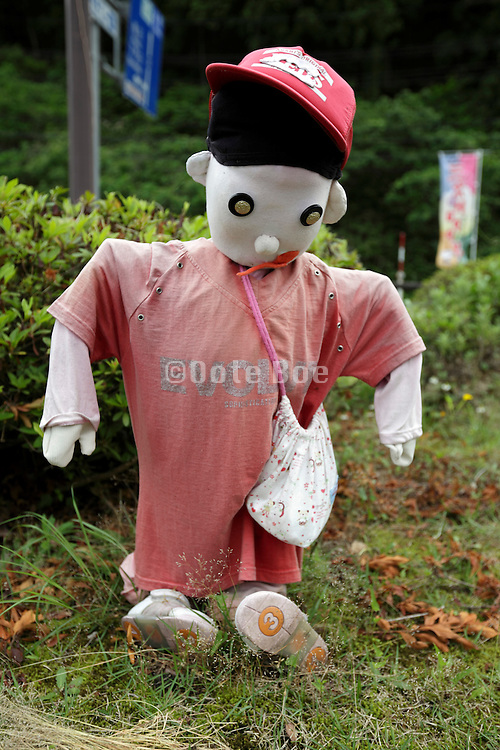 stuffed human child figure at the side of the road