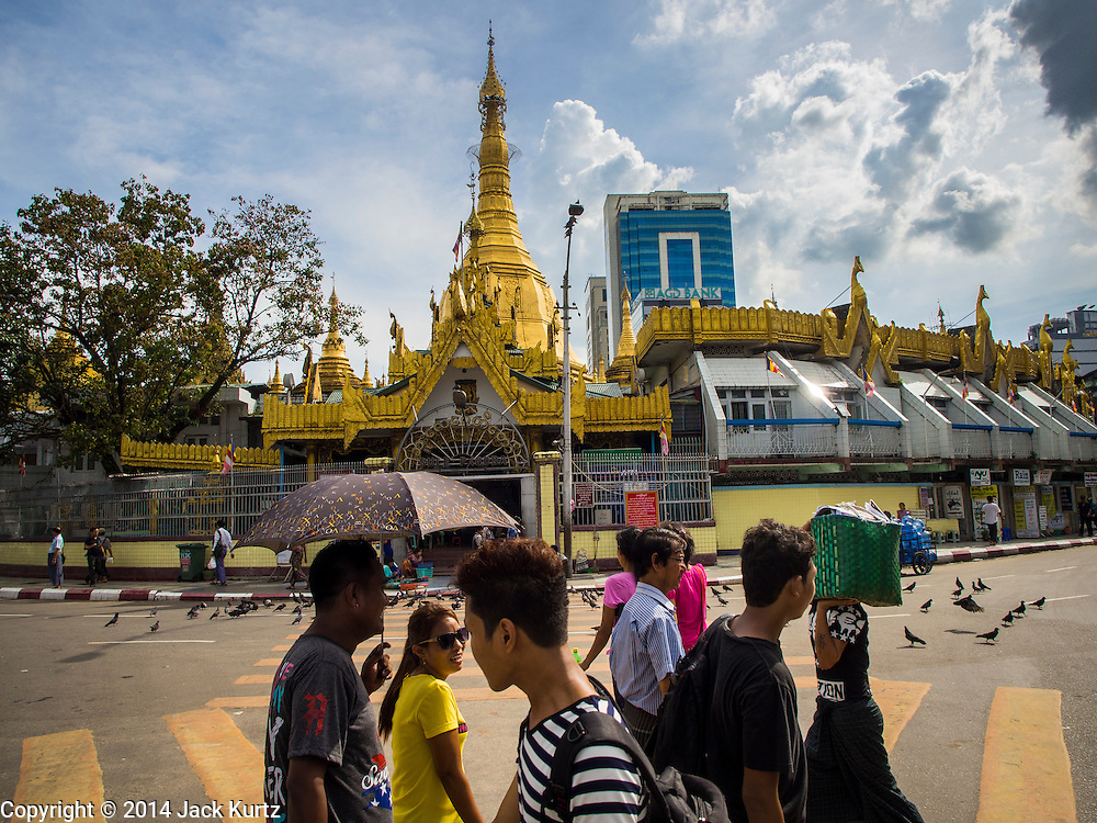 01 NOVEMBER 2014 - YANGON, MYANMAR: People cross Sule Road in front of Sule Pagoda in Yangon. Sule Pagoda is one of the oldest temples in Yangon. In the past it was used as a rallying point for pro-democracy protestors.     PHOTO BY JACK KURTZ
