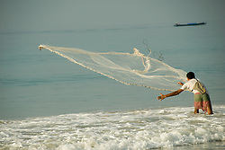 A fisherman casts his net, hoping to catch a passing school of fish.  Havelock Island, Andaman Islands, Andaman Sea, India