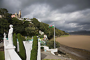 """Portmeirion, in North Wales, is a resort, where no one has ever lived. A self-taught Welsh architect named Sir Clough Williams-Ellis built it out of architectural salvage between the 1920s and 1970s, loosely based on his memories of trips to Portofino. Including a pagoda-shaped Chinoiserie gazebo, some Gothic obelisks, eucalyptus groves, a crenellated castle, a Mediterranean bell tower, a Jacobean town hall, and an Art Deco cylindrical watchtower. He kept improving Portmeirion until his death in 1978, age 94. It faces an estuary where at low tide one can walk across the sands and look out to sea. At high tide, the sea is lapping onto the shores. Every building in the village is either a shop, restaurant, hotel or self-catering accomodation. The village is booked out at high season, with numerous wedding receptions at the weekends. Very popular amongst the English and Welsh holidaymakers. Many who return to the same abode season after season. Hundreds of tourists visit every day, walking around the ornamental gardens, cobblestone paths, and shopping, eating ice-creams, or walking along the woodland and coastal paths, amongst a colourful assortment of hydrangea, rhododendrons, tree ferns and redwoods. The resort boasts two high class hotels, a la carte menus, a swimming pool, a lifesize concrete boat, topiary, pools and wishing wells. The creator describes the resort as """"a home for fallen buildings,"""" and its ragged skyline and playful narrow passageways which were meant to provide """"more fun for more people."""" It does just that.///Promenade, at Hotel Portmeirion,  with statues overlooking the estuary, the swimming pool and the village behind on the hill"""