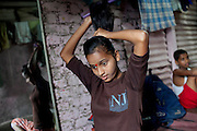Mayuri Mahesh Pandit, 13, (centre) is sitting insider her home tiding her hair, just before attending the Unicef-run 'Deepshikha Prerika' project inside the Milind Nagar Pipeline Area, an urban slum on the outskirts of Mumbai, Maharashtra, India, where she resides with her family.