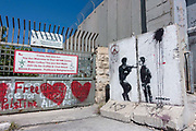 Original Banksy street art on the partition wall which annexes Palestinian land to Israel in the West Bank city of Bethlehem on 1st April 2016 in Bethlehem, West Bank. During the Palestine Marathon, thousands of runners, both professional and amateur come from across the globe to take part in the Right to Movement event.