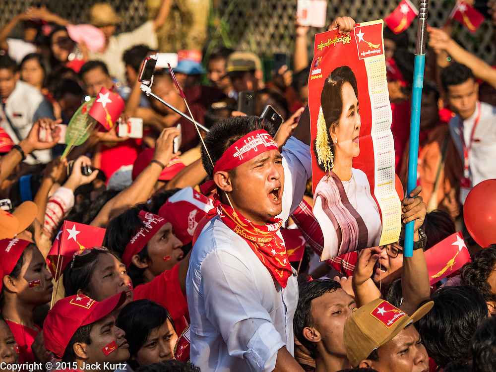 01 NOVEMBER 2015 - YANGON, MYANMAR: A man holds up a photo of Aung San Suu Kyi, leader of the oppositon NLD, while he waits for her to arrive at a NLD rally near Yangon Sunday. Political parties are wrapping up their campaigns in Myanmar (Burma). National elections are scheduled for Sunday Nov. 8. The two principal parties are the National League for Democracy (NLD), the party of democracy icon and Nobel Peace Prize winner Aung San Suu Kyi, and the ruling Union Solidarity and Development Party (USDP), led by incumbent President Thein Sein. There are more than 30 parties campaigning for national and local offices.    PHOTO BY JACK KURTZ
