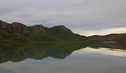 The cliffs of Talbot Bay reflect in still water in the Kimberley wet season.