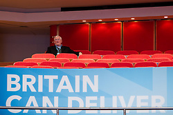 © Licensed to London News Pictures. 07/10/2012. Birmingham , UK . A delegate in the audience sits alone above a Britain Can Deliver banner . Conservative Party Conference Day 1 at the International Convention Centre . Photo credit : Joel Goodman/LNP