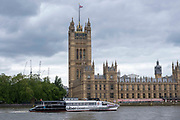 An Uber Boat by Thames Clippers travelling along the river Thames past the House of Commons in central London on the 25th of May 2021.