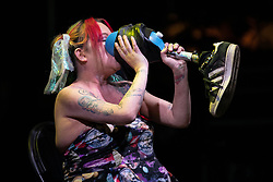 © Licensed to London News Pictures . 26/08/2019. Manchester, UK. JACKIE HAGAN drinks lager from her artificial leg . A candlelit vigil , organised by the George House Trust , in memory of the victims of HIV and AIDS , takes place in Sackville Gardens in Manchester's Gay Village , at the close of 2019's Manchester Pride . Photo credit: Joel Goodman/LNP