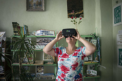 July 23, 2017 - Kryva Luka, Donetsk, Ukraine - Yana Synytsia wears virtual reality glasses in a village club in Kryva Luka in Donetsk region, ATO zone, Ukraine on July 24, 2017. Yana is a refugee from Donetsk. She had a tourism agency in the city but in 2014 she decided to move to non-occupied area when fighting at the area had started. Now the woman develops tourism in the region as it has unique nature and is situated in Cretaceous flora nature park. Yana hopes to use modern technologies to show the beauties of the place. Now tourists can see places of nature park through virtual reality glasses in the local club which is also museum of the village  (Credit Image: © Oleksandr Rupeta/NurPhoto via ZUMA Press)
