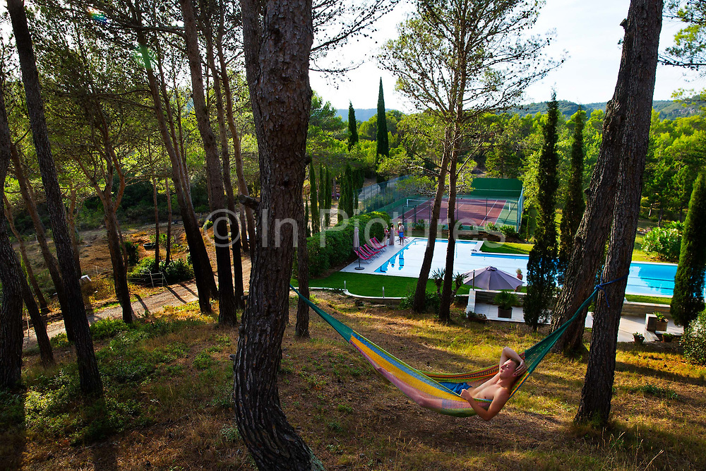 Man sleeping in hammock in the grounds of a country holiday house, 25th August 2014, Lagrasse France.