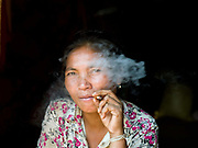 A Khmu ethnic minority woman smoking a homemade cigarette in her home in the remote and roadless village of Ban Nam Houn, Phongsaly province, Lao PDR. Ban Nam Houn is situated along the Nam Houn river (a tributary of the Nam Ou).