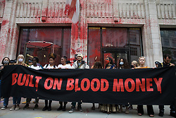 Environmental activists from Extinction Rebellion stand behind a banner outside the Guildhall after it was sprayed with blood-red paint during a Blood Money March through the City of London on 27th August 2021 in London, United Kingdom. Extinction Rebellion were intending to highlight financial institutions funding fossil fuel projects, especially in the Global South, as well as law firms and institutions which facilitate them, whilst calling on the UK government to cease all new fossil fuel investment with immediate effect.