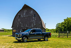 2021 Ford F150 King Ranch Super Crew in Smoked Quartz and Chrome posed in front of an old barn located at Moraine View State Park