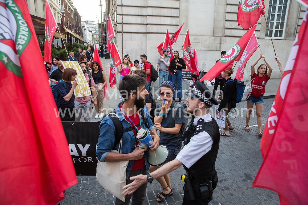 London, UK. 12 July, 2019. A police officer speaks to members of the Cleaners and Facilities Branch of the IWGB (Independent Workers of Great Britain) trade union protesting outside 5 Hertford Street in Mayfair, which also houses exclusive private club Loulou's, to call for its kitchen porters, recently outsourced through ACT Clean, to be paid the London Living Wage and given terms and conditions including suitable sick pay, holidays and pension contributions. Numerous unmarked security guards were present outside the venue.