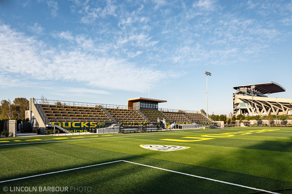 Architectural photo of University of Oregon's Women's Soccer & Lacrosse Stadium. Designed by DLR Group. A view of the bleachers from one end of the field.  Blue skies overhead with some thin clouds.