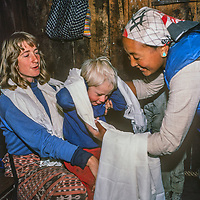 Lakpa Doma Sherpa presents ceremonial kata prayer scarves to 3-year old Ben Wiltsie & mother Meredith at her home in Namche Bazaar,leading town of the Khumbu region of Nepal.