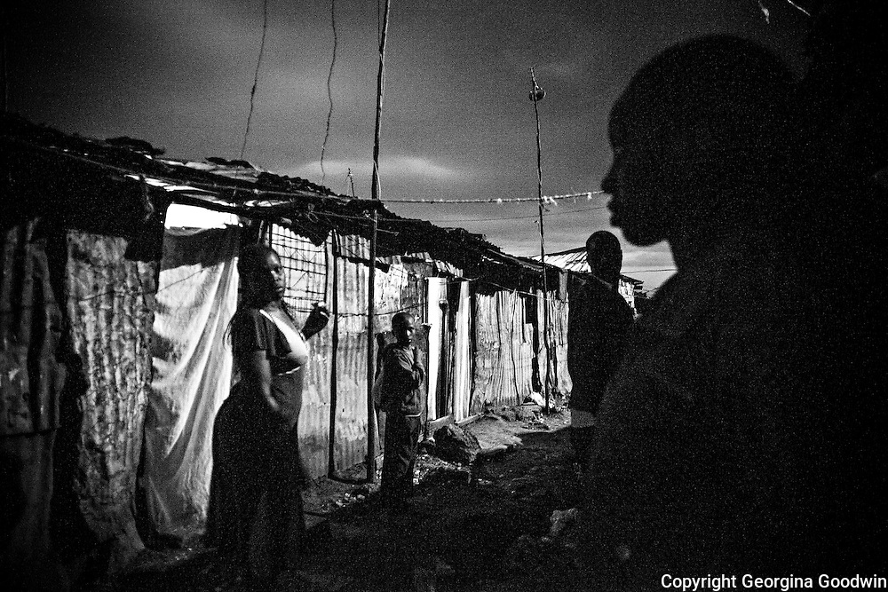 Night closes in on the bottom end of Kawangware Street, the area where many rape incidences have occurred. Since the installation of the flood light further down in December 2012, a joint initiative of the Kenya Government and Safaricom who pay the electricity fee, the incidences of rape have been reduced. <br /> This image is from a series focusing on and around the rape and the women victims that occur every half a day in Mugumoini Village in Nairobi's Southlands, a slum home to 20,000 people in abject poverty with little or no income, with the aim of creating exposure and empowerment for change. ©GGoodwin