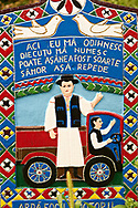 Tombstone of a lorry owner and lorry,  The  Merry Cemetery ( Cimitirul Vesel ),  Săpânţa, Maramares, Northern Transylvania, Romania.  The naive folk art style of the tombstones created by woodcarver  Stan Ioan Pătraş (1909 - 1977) who created in his lifetime over 700 colourfully painted wooden tombstones with small relief portrait carvings of the deceased or with scenes depicting them at work or play or surprisingly showing the violent accident that killed them. Each tombstone has an inscription about the person, sometimes a light hearted  limerick in Romanian. .<br /> <br /> Visit our ROMANIA HISTORIC PLACXES PHOTO COLLECTIONS for more photos to download or buy as wall art prints https://funkystock.photoshelter.com/gallery-collection/Pictures-Images-of-Romania-Photos-of-Romanian-Historic-Landmark-Sites/C00001TITiQwAdS8