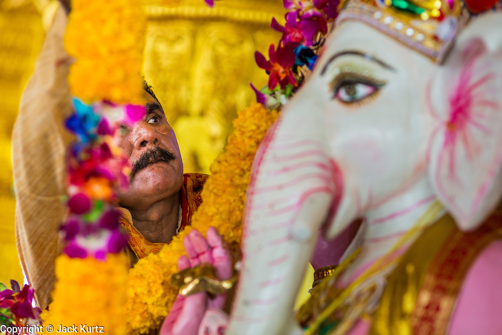 """15 SEPTEMBER 2013 - BANGKOK, THAILAND: A Hindu priest places a garland of marigolds on a deity (statue) of Ganesha on the last day of Ganesha Chaturthi celebrations at Shiva Temple in Bangkok. Ganesha Chaturthi is the Hindu festival celebrated on the day of the re-birth of Lord Ganesha, the son of Shiva and Parvati. The festival, also known as Ganeshotsav (""""Festival of Ganesha"""") is observed in the Hindu calendar month of Bhaadrapada. The festival lasts for 10 days, ending on Anant Chaturdashi. Ganesha is a widely worshipped Hindu deity and is revered by many Thai Buddhists. Ganesha is widely revered as the remover of obstacles, the patron of arts and sciences and the deva of intellect and wisdom. The last day of the festival is marked by the immersion of the deity, which symbolizes the cycle of creation and dissolution in nature. In Bangkok, the deity (statue) was submerged in the Chao Phraya River.     PHOTO BY JACK KURTZ"""