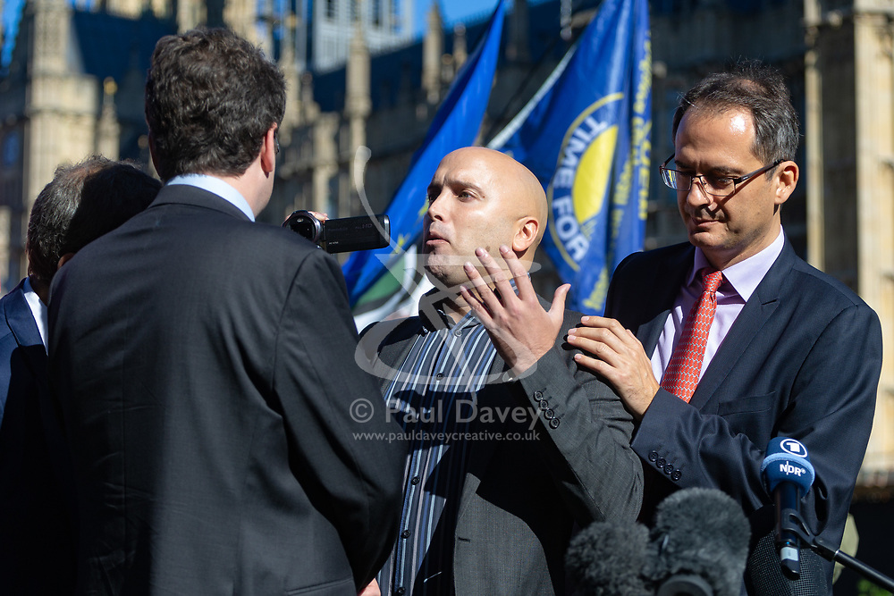 Elliot Higgins, left, Founder of investigative website Bellingcat and investigator Christo Grozev, right are confronted by a protester accusing them of working for NATO at a press conference on College Green opposite the Houses of Parliament. London, October 09 2018.