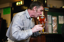 Man carrying drinks in a pub,