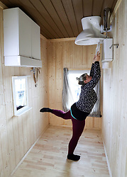 An employee holds onto the toilet seat in the bathroom in 'The Upside Down House', a zero-gravity illusion experience, in The Triangle in Bournemouth, Dorset.